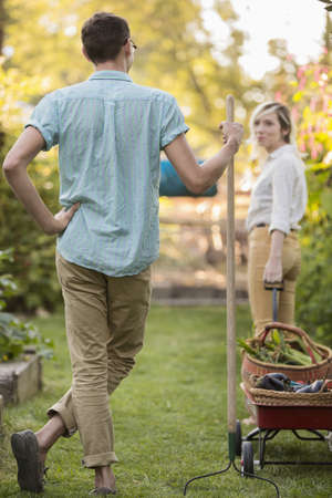 Couple with rake and baskets in garden