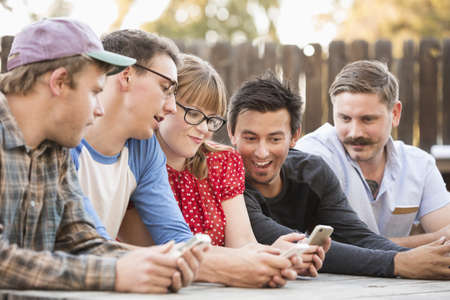 Friends using cell phone together in backyard