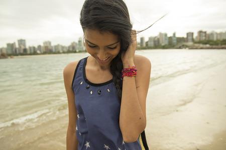 Smiling woman walking on urban beach LANG_EVOIMAGES