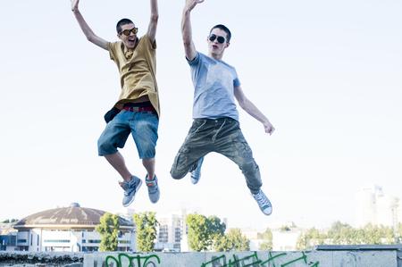 Caucasian men jumping for joy in city