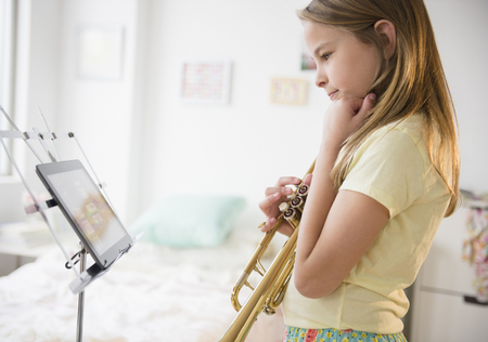 Caucasian girl practicing trumpet with digital tablet