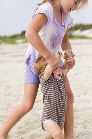 Caucasian girl playing with baby brother on beach