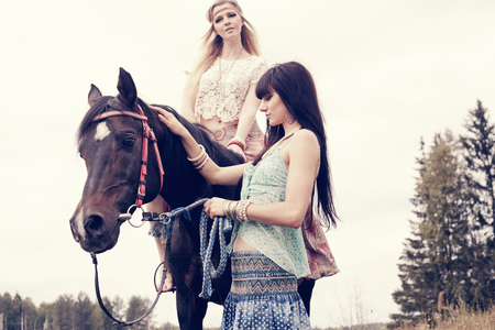 Caucasian women petting and riding horse outdoors