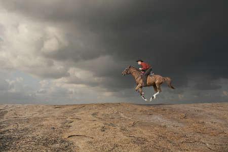 Caucasian cowboy riding horse in rocky landscape LANG_EVOIMAGES