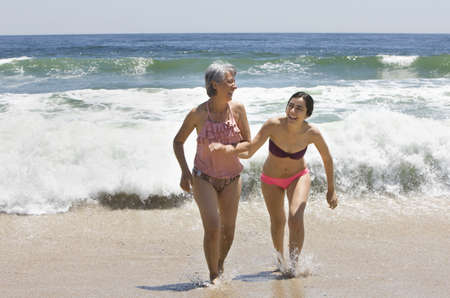 Hispanic mother and daughter playing in waves on beach