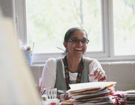 Indian teacher smiling at desk in classroom LANG_EVOIMAGES