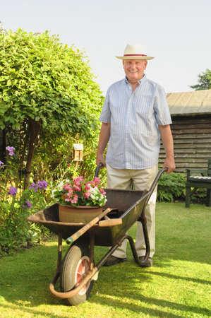 Caucasian man pushing wheelbarrow in backyard LANG_EVOIMAGES