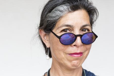Older Hispanic woman wearing blue sunglasses