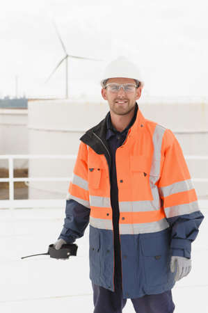 Caucasian technician holding walkie-talkie on fuel storage tank