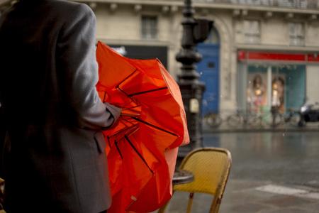 Close up of woman opening umbrella on rainy city street