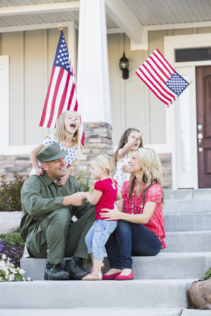 Caucasian soldier and family playing together on front stoop