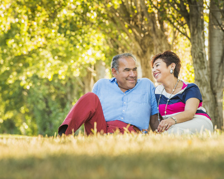 Older Hispanic couple sitting in grassy field