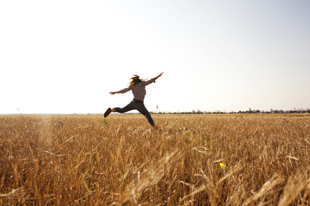 Caucasian woman jumping for joy in rural field