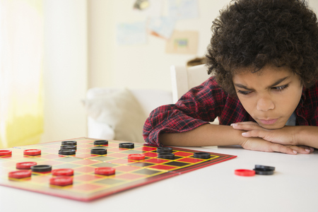 Angry mixed race boy losing game of checkers
