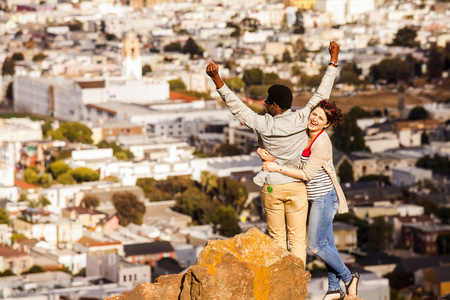 Couple cheering near scenic view of cityscape LANG_EVOIMAGES