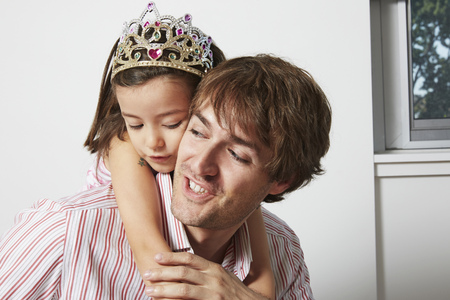 Father carrying daughter in tiara