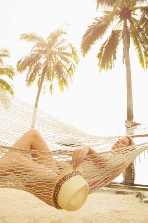 Caucasian woman napping in hammock LANG_EVOIMAGES