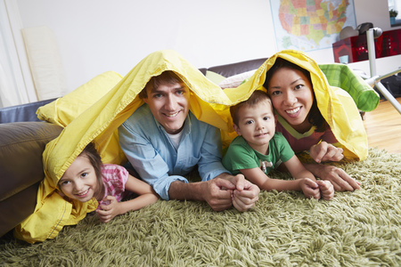 Family playing in blanket fort in living room