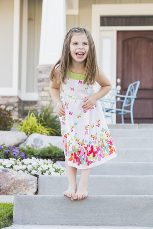 Laughing Caucasian girl standing on front stoop LANG_EVOIMAGES