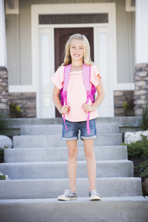 Caucasian girl with backpack smiling on front stoop