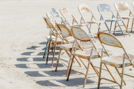 Dilapidated chairs arranged in circle in dirt field