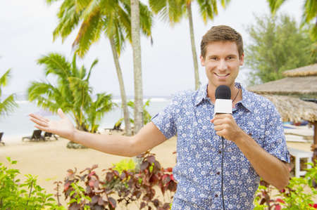 Caucasian television presenter reporting on tropical beach LANG_EVOIMAGES