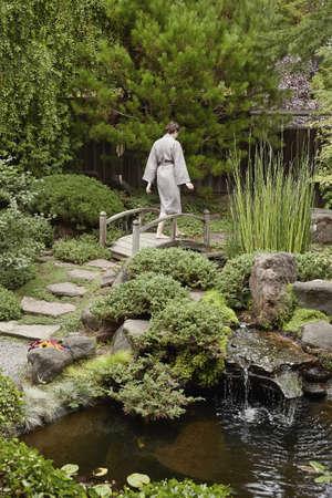 Caucasian woman in robe walking in zen garden