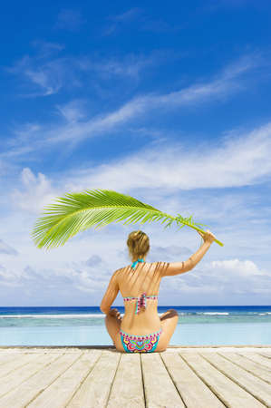 Caucasian woman shading herself with palm frond near swimming pool