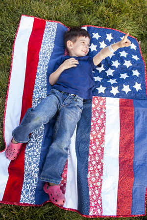 Mixed race boy pointing up on American flag blanket on grass