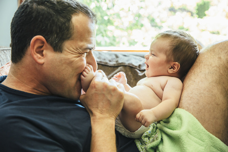 Caucasian father kissing feet of baby boy