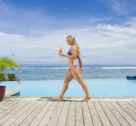 Caucasian woman carrying cocktail on wooden dock LANG_EVOIMAGES