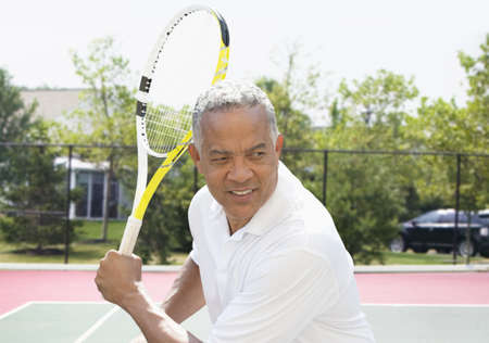 African American man playing tennis on court