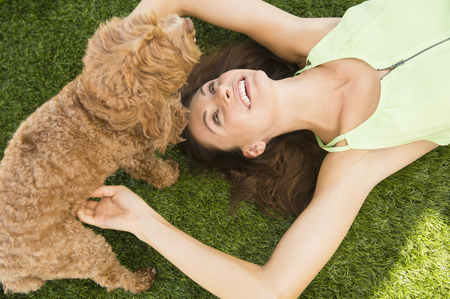 Caucasian woman playing with dog on lawn LANG_EVOIMAGES