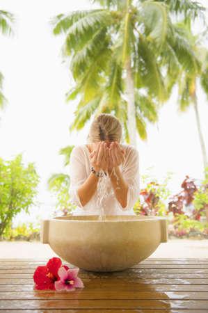 Caucasian woman washing face in spa bath