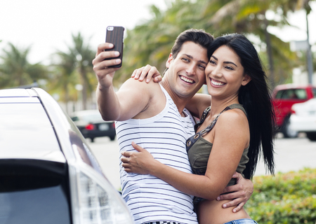 Hispanic couple taking cell phone selfie outdoors