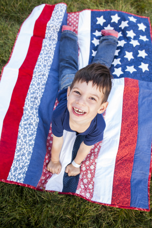 Mixed race boy laying on American flag blanket on grass LANG_EVOIMAGES
