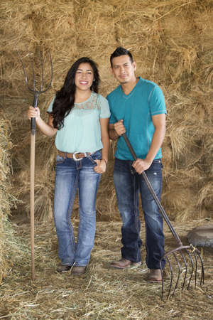 Hispanic couple holding pitchforks near hay in barn LANG_EVOIMAGES