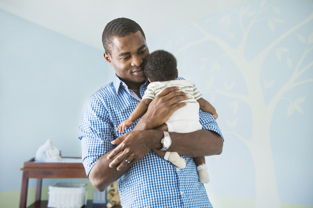 Father cradling baby son LANG_EVOIMAGES