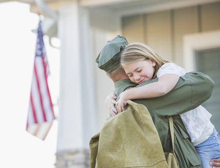 Returning Caucasian soldier hugging daughter
