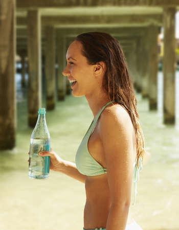 Pacific Islander woman drinking water under wooden pier on beach