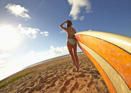 Pacific Islander woman carrying surfboards on beach