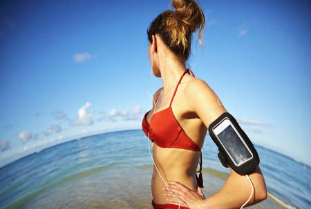 Pacific Islander woman listening to mp3 player near ocean LANG_EVOIMAGES