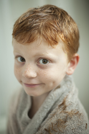 Caucasian boy wrapped in towel after haircut LANG_EVOIMAGES