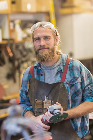 Caucasian craftsman smiling in workshop