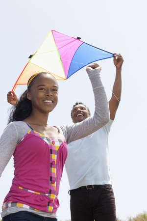 Father and daughter flying a kite together