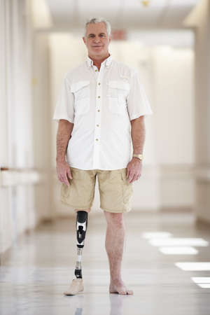 Patient with artificial leg standing in hospital corridor LANG_EVOIMAGES