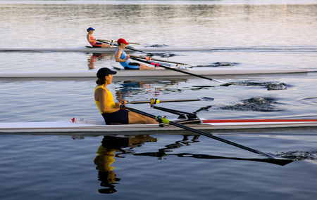 People rowing sculling boats on river LANG_EVOIMAGES