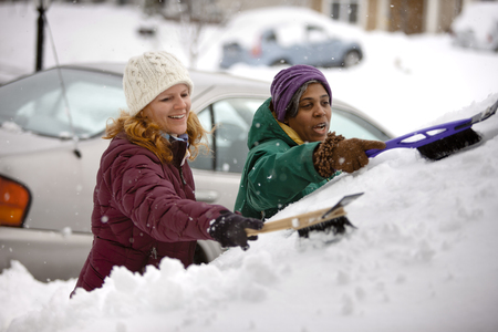 Two women scraping snow from windshield LANG_EVOIMAGES