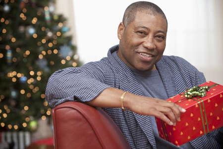 Black man holding gift in living room at Christmastime LANG_EVOIMAGES