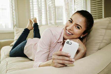 Caucasian woman using cell phone on sofa LANG_EVOIMAGES